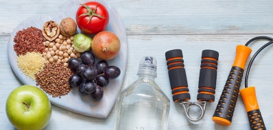 a-variety-of-healthy-grains-vegetables-fruit-and-exercise-equipment-on-a-wooden-table
